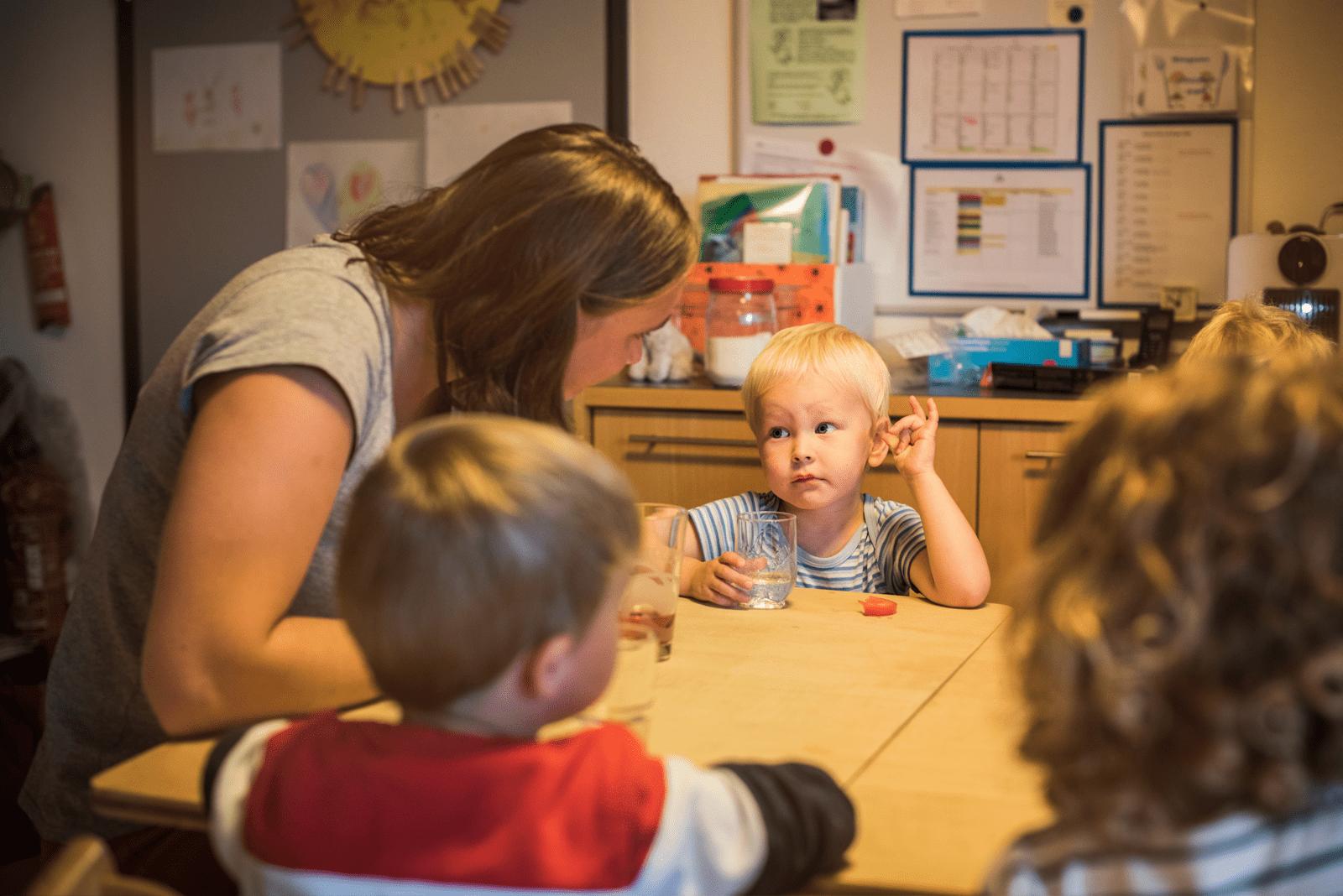 Kita-Betreuerin plaudert mit Kindern am Tisch
