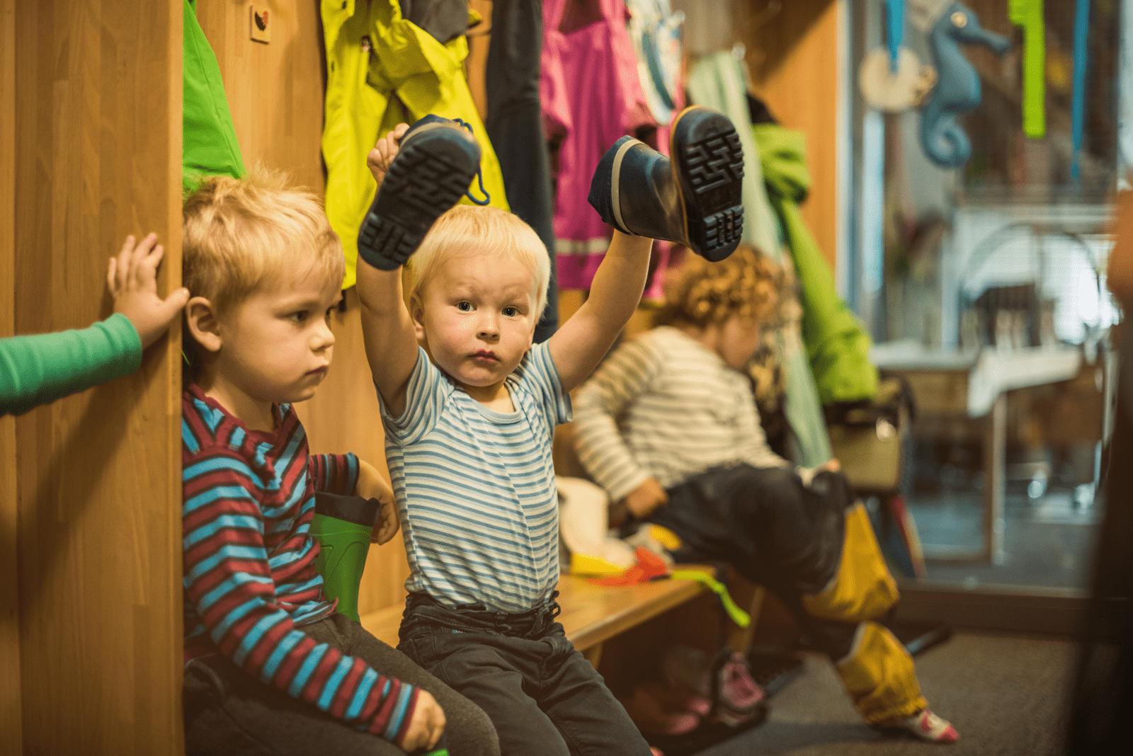 Kinder ziehen sich in der Garderobe um. Junge hält Gummistiefel in die Höhe.