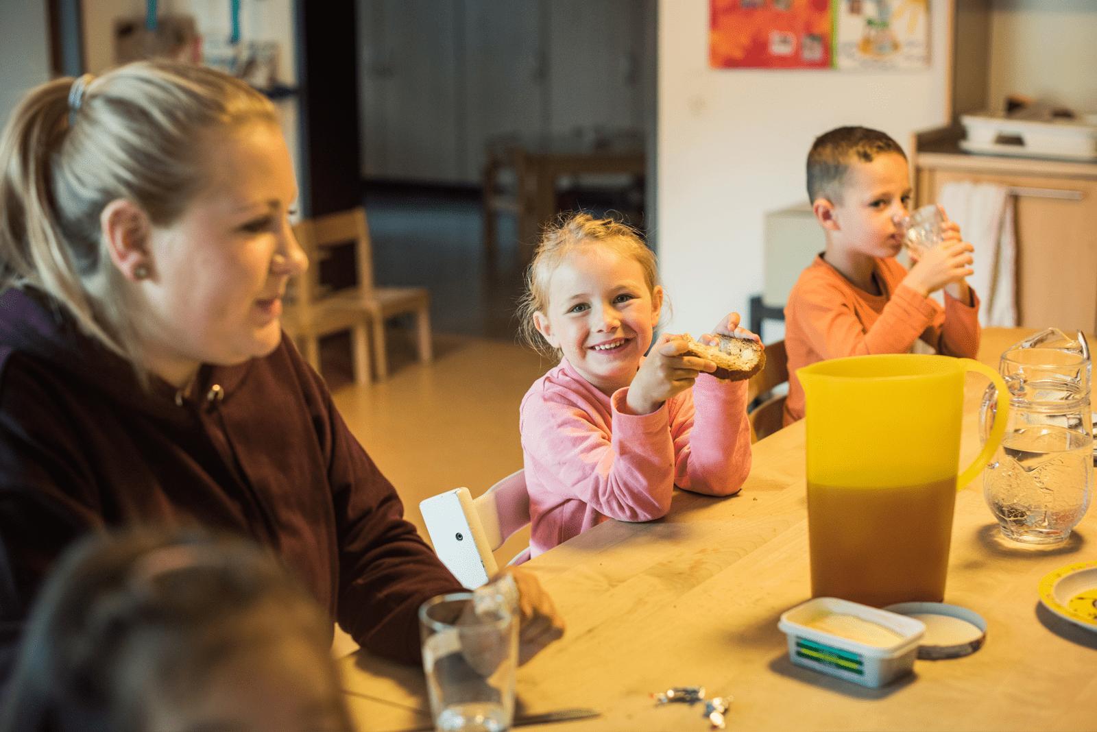 Mädchen sitzt genüsslich am Tisch mit Zvieribrot in der Hand.