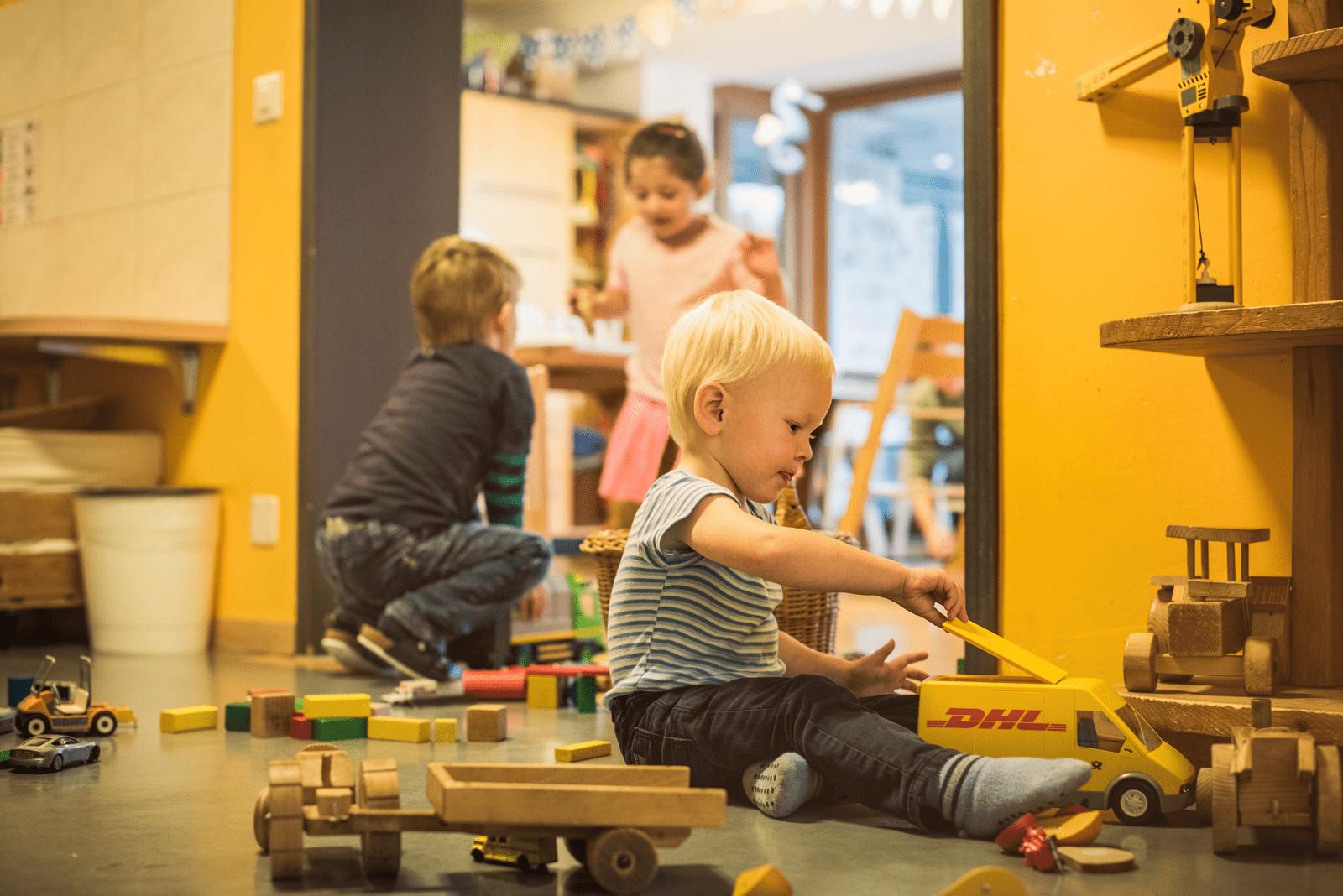 Kinder sind mit Holzspielzeug am Spielen.