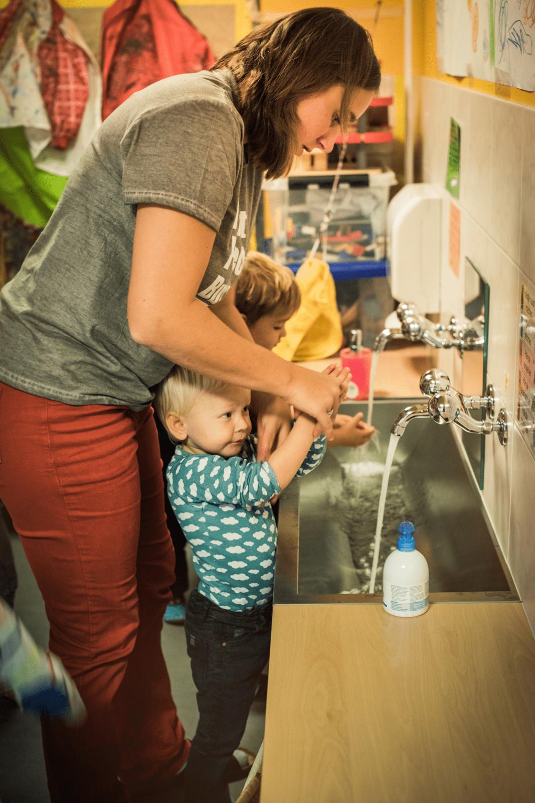 Betreuerin wäscht mit Junge zusammen die Hände nach dem Essen.