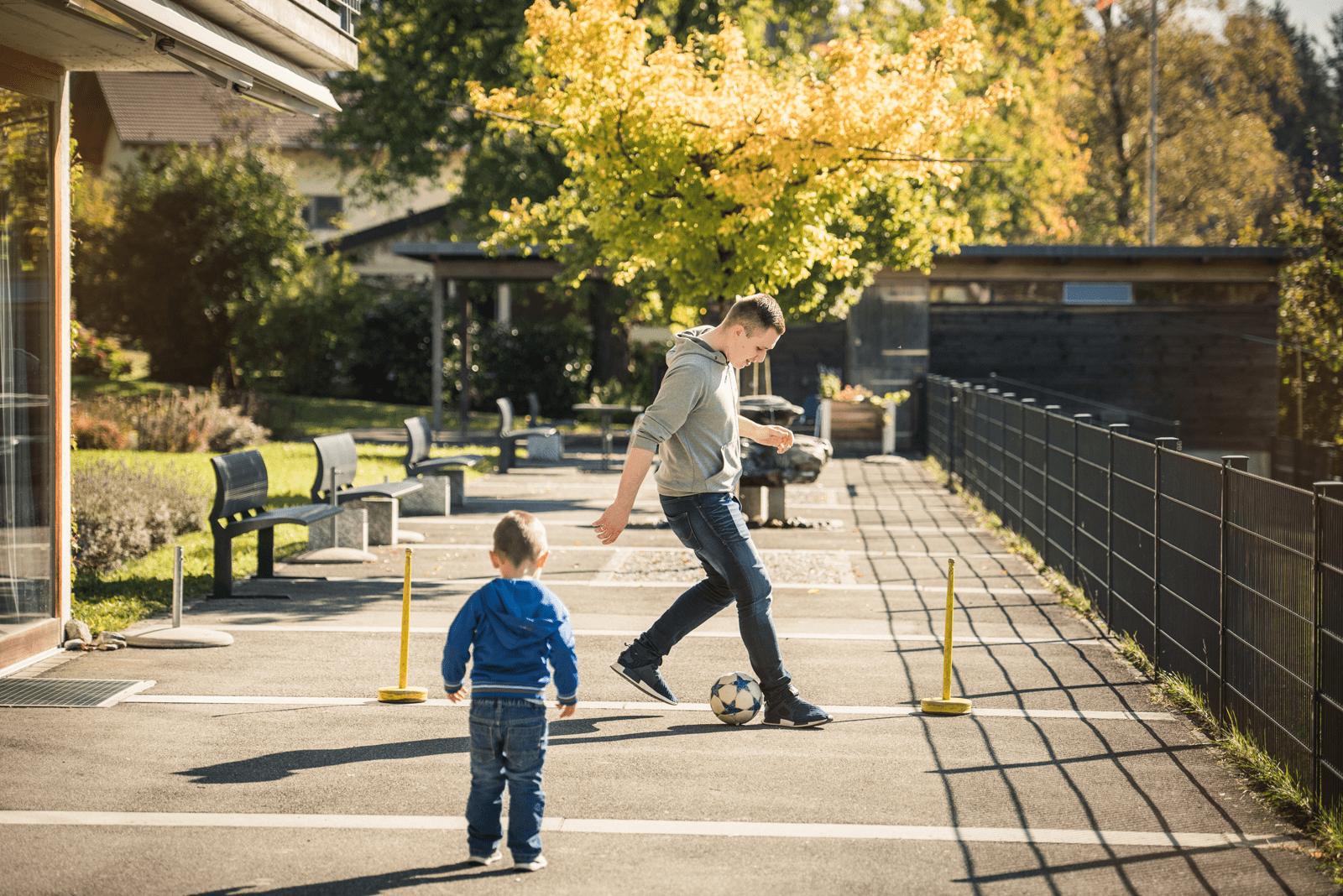 Hier spielen die Fussballprofis. Kinderbetruer spielt mit Knabe draussen Fussball.