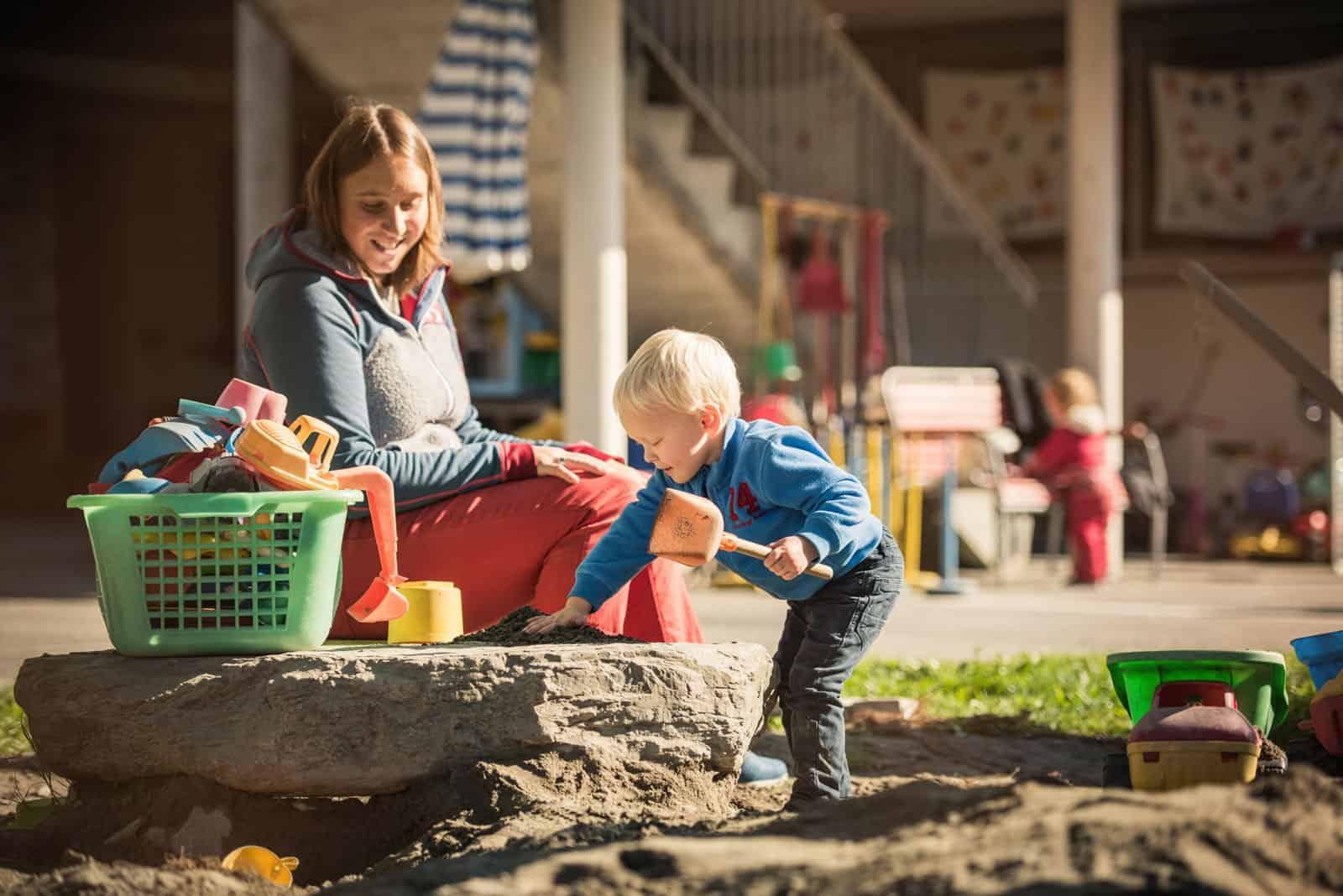 Kinder sind im Sandkasten von der Kita Chinderhus Brienz am spielen.