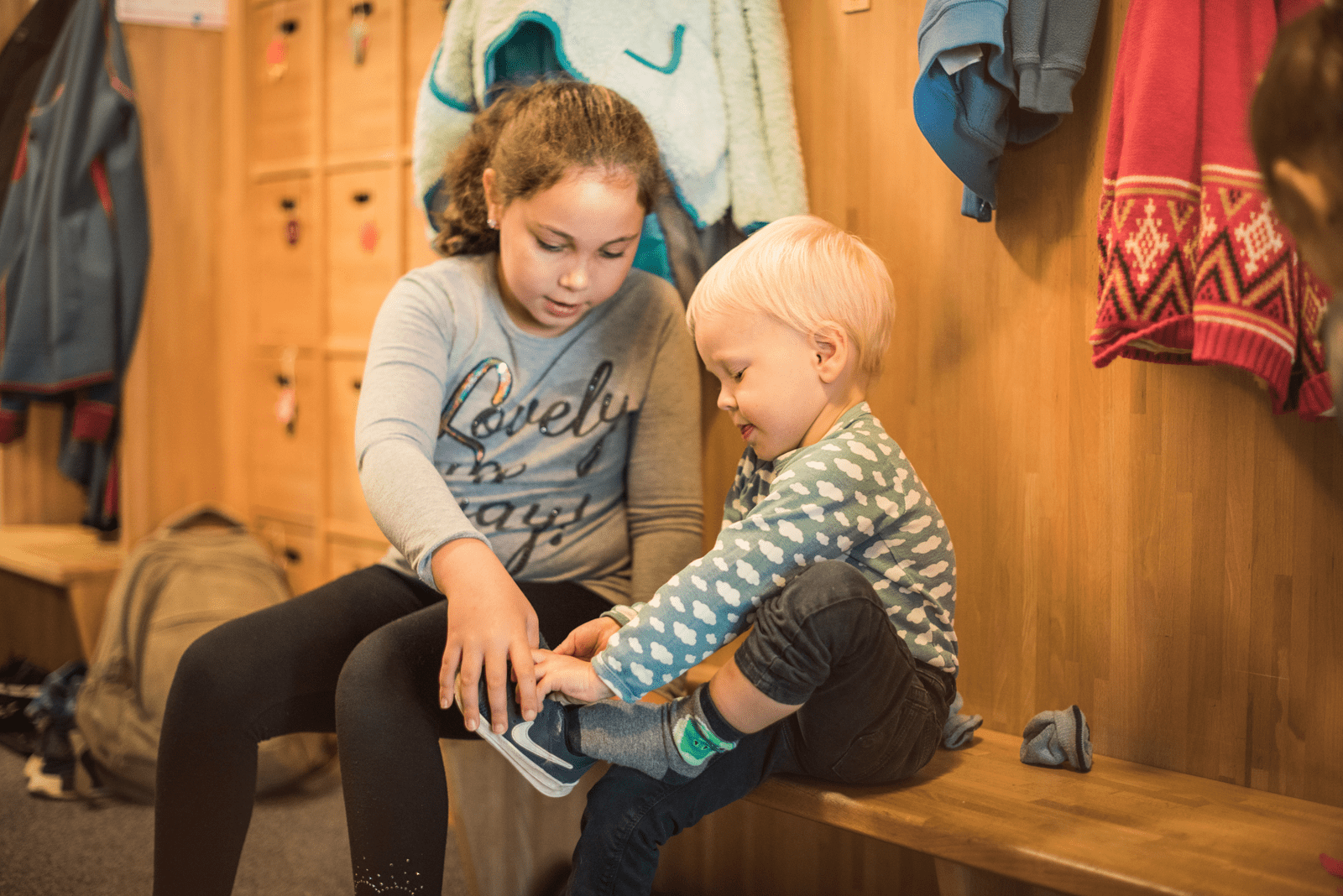Mädchen aus Kindertagesstätte hilft einem Jungen die Schuhe anzuziehen.