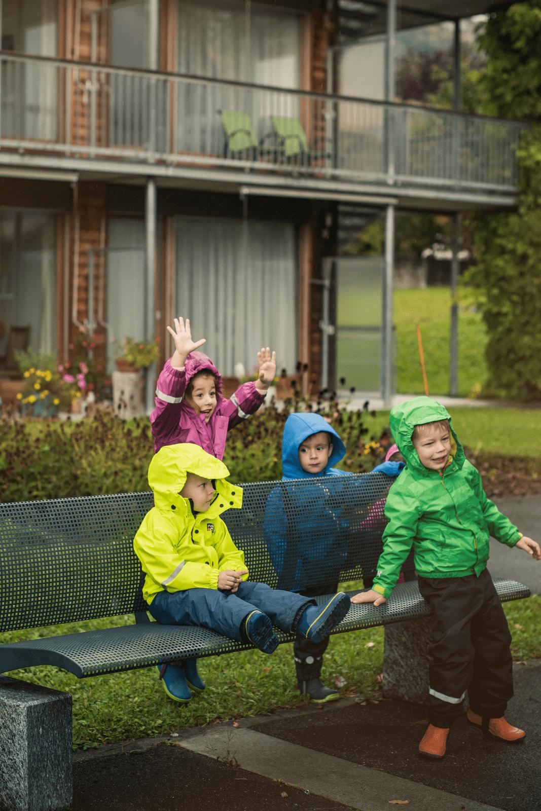 Kita-Kinder haben trotz Regenwetter draussen gute Laune beim Spielen.