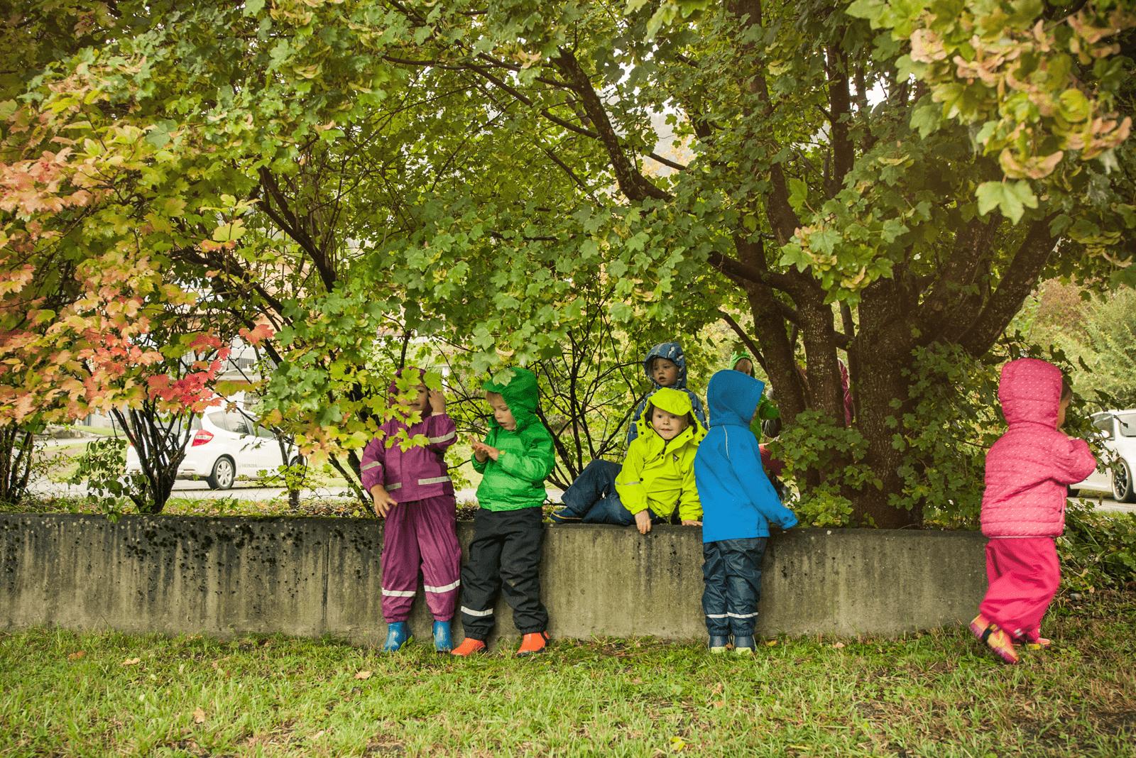 Kinder vom Chinderhus Brienz spielen bei Regenwetter unter dem Baum.