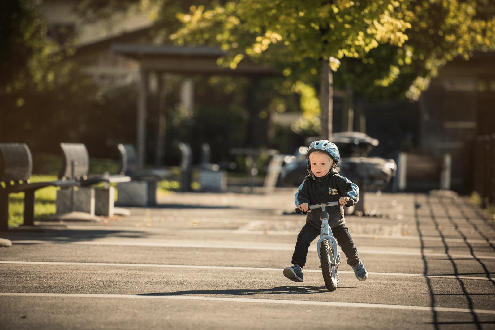Kleiner Junge fährt mit Vollgas vor der Kita mit dem Fahrrad und hat sichtlich Spass dabei.