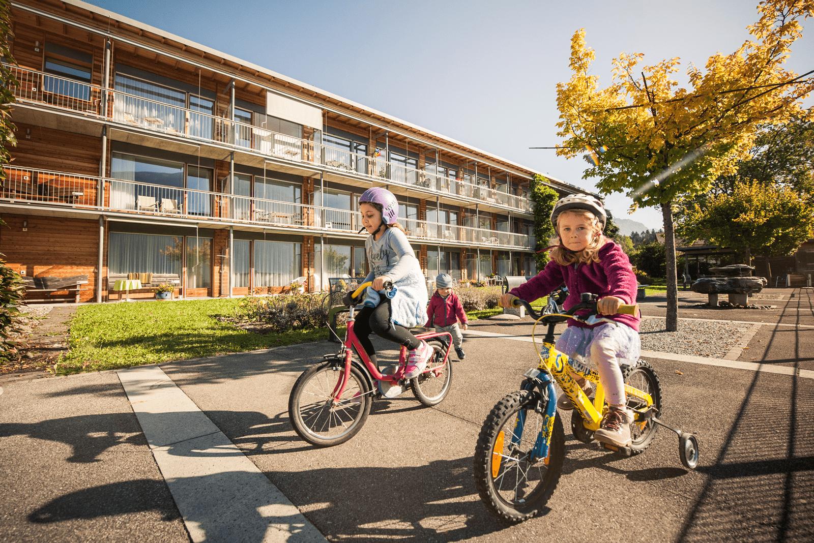 Mädchen fahren draussen Fahrrad.
