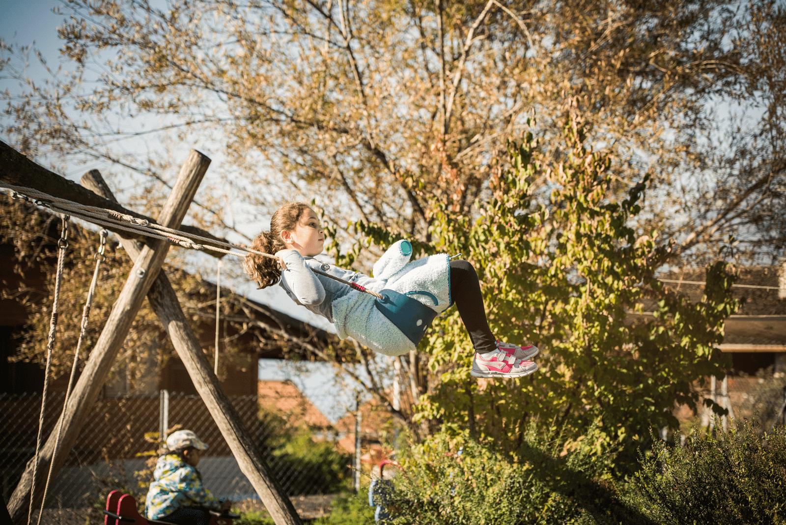 Mädchen auf dem Spielplatz am Schaukeln.