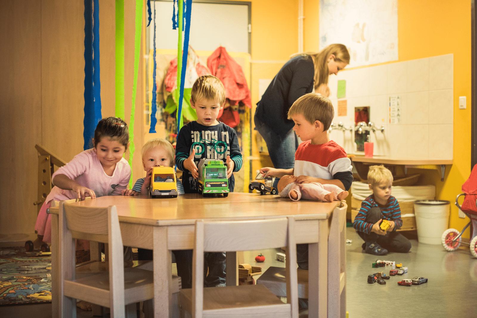 Kinder zeigen stolz ihre Autos die sie zum Spielen haben.