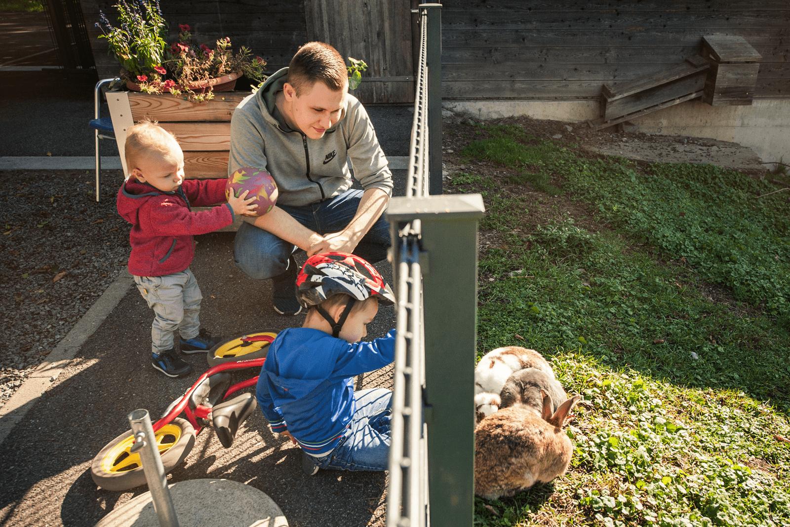 Kinderbetreuer ist mit Kindern bei den Birgli Hasen zu Besuch.