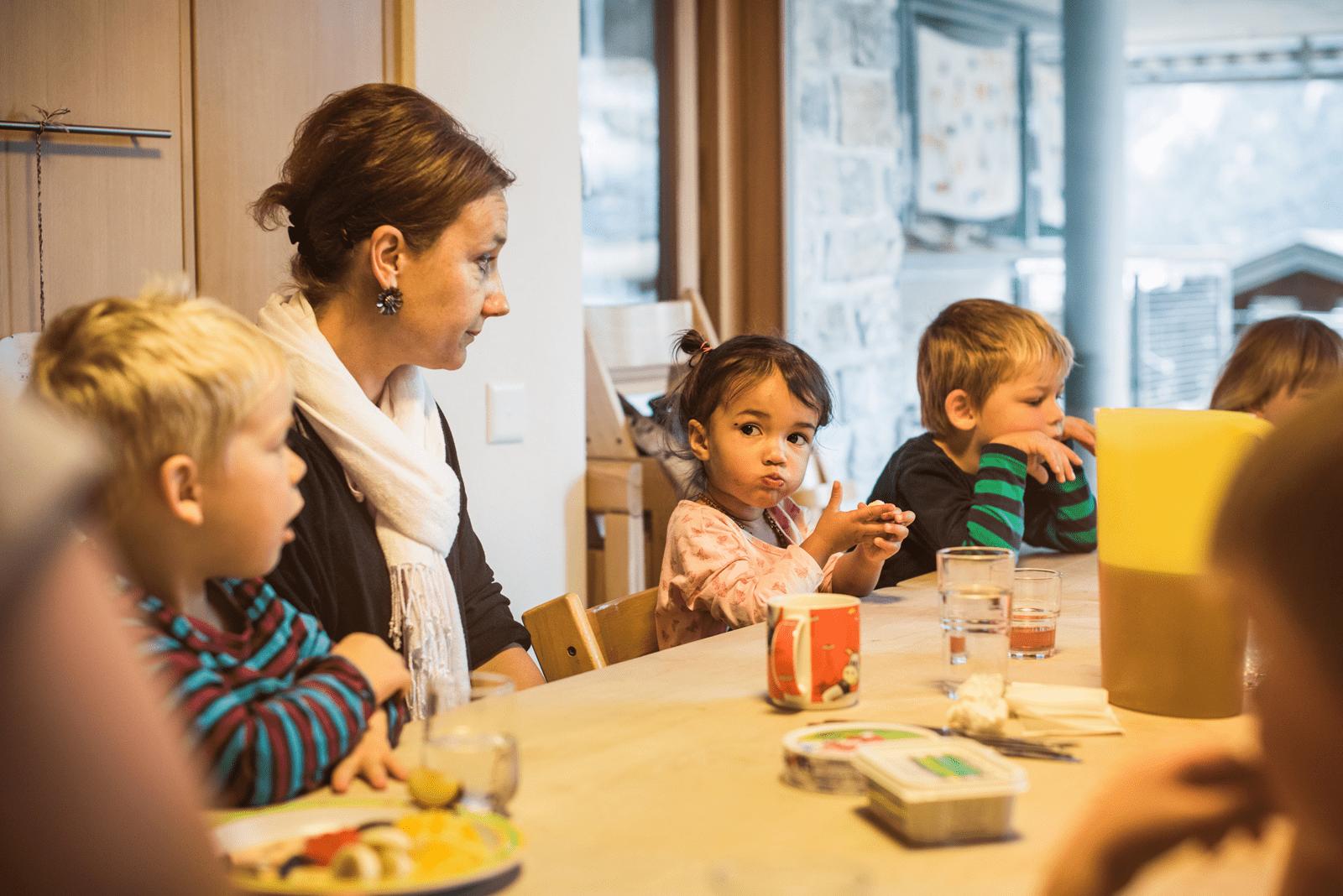 Kinder und Kita-Leiterin sitzen am Tisch und essen Znüni.