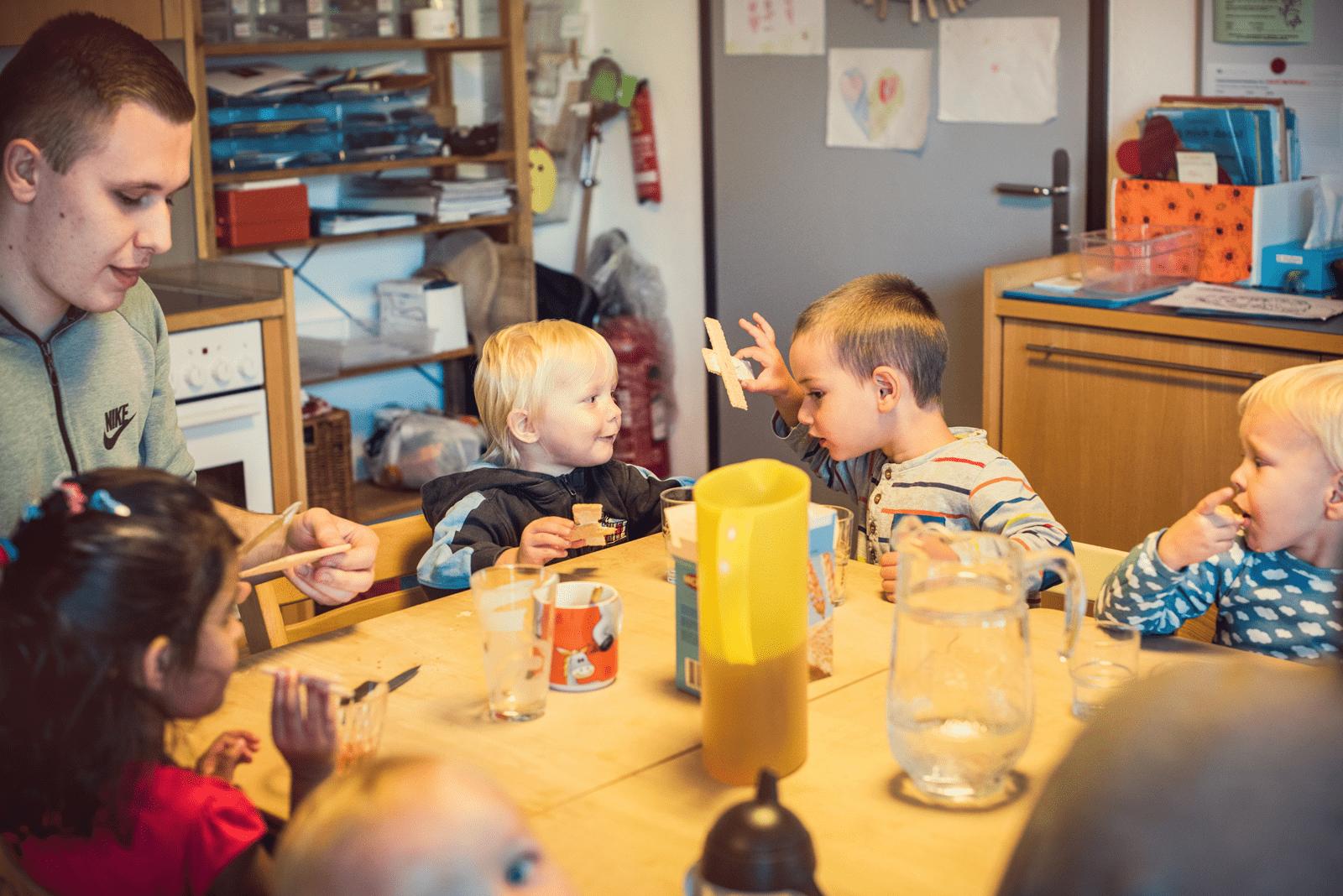 Alltagssituation in Kita, Kinder sitzen am Tisch und essen Zvieri.